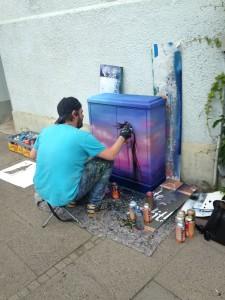 Vor einem zartwolkigen Hintergund entsteht mit feingesetzten Sprühstößen eine Frauengestalt. Wie auf dem vorigen Foto sind um den Künstler herum etliche Spraydosen verteilt, er selbst sitzt hier auf einem kleien Hocker.