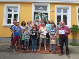 17 Erwachsene und zwei Kinder posieren mit Putzzeug und Bildentwürfen vor einem schönen Hauseingang im Lollfuß.