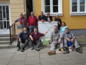 10 Leute aus dem Lollfuß haben sich um einen gesäuberten ud grundierten Stromverteilerkasten vor einem Haus gruppiert. Einige tragen Arbeitskleidung, einer hält einen Pinsel hoch.