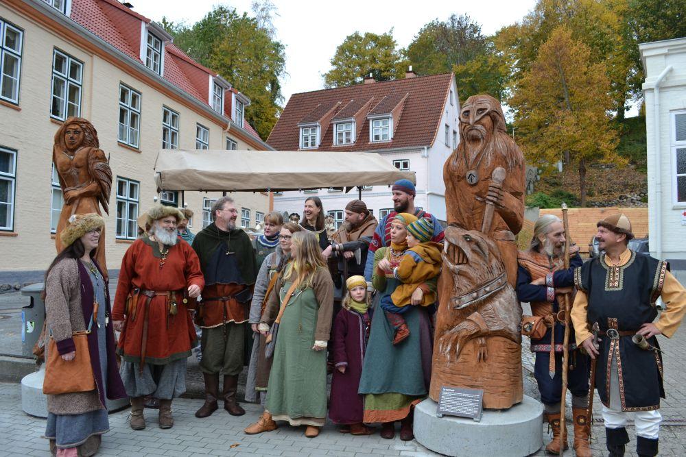 Auf diesem Foto stehen Personen in wikingerzeitlicher Kleidung um die beiden großen Holzfiguren herum.