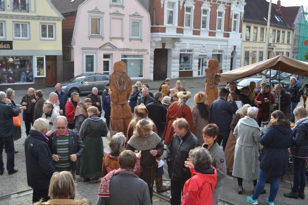 Auf dem Foto ist der Gehweg voll von menschen, die um die Holzfiguren und den danebenstehenden Infostand stehen und miteinander im Gespräch sind.