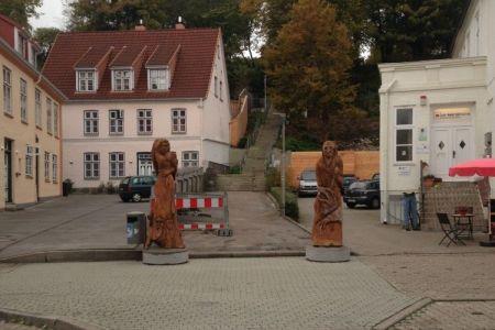 Die beiden Holzfiguren am Fuße der Lollfußtreppe, diesmal ohne Menschenmenge.