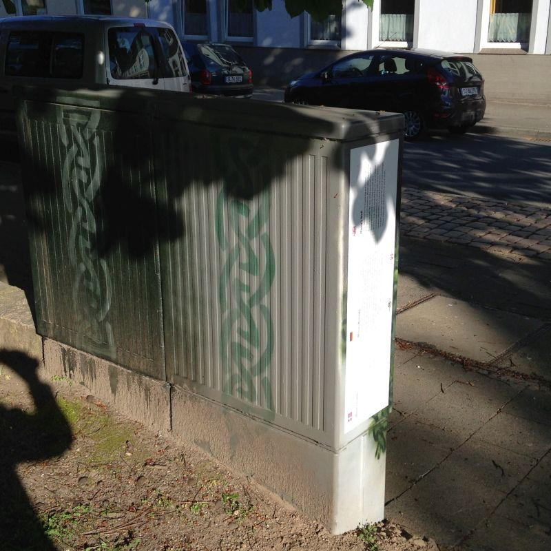Die Rückseite des Stromkastens vor dem Amtsgericht. Sie ist mit zwei Flechtbändern verziert.