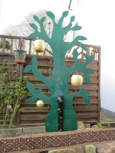 Ein Baum, der aus einer grün angetrichenen Holzplatte besteht, die in Form eines verzweigten Baumes ausgesägt ist. An einigen Ästen hängen goldene Äpfel in verschiedenen Größen.