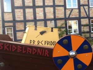 Ansicht der einen Vorderseite des Schiffes. Der Name ist aus Holzbuchstaben am Bug. Auf der Seite der Kiste ist die gezeichnete Kornähre und der Runenspruch zu sehen.
