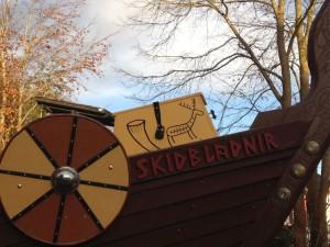 Ansicht der Bugseite mir dem Schiffsnamen aus Holzbuchstaben und einem der Schilde. Auf der an Deck stehende Kiste ein Trinkhorn und eine Hirschdarstelllung.
